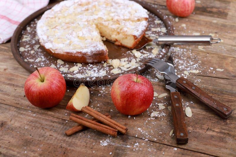 сладкий домашний яблочный торт с корицей и свежими яблоками на заросшем деревянном столе стоковые изображения