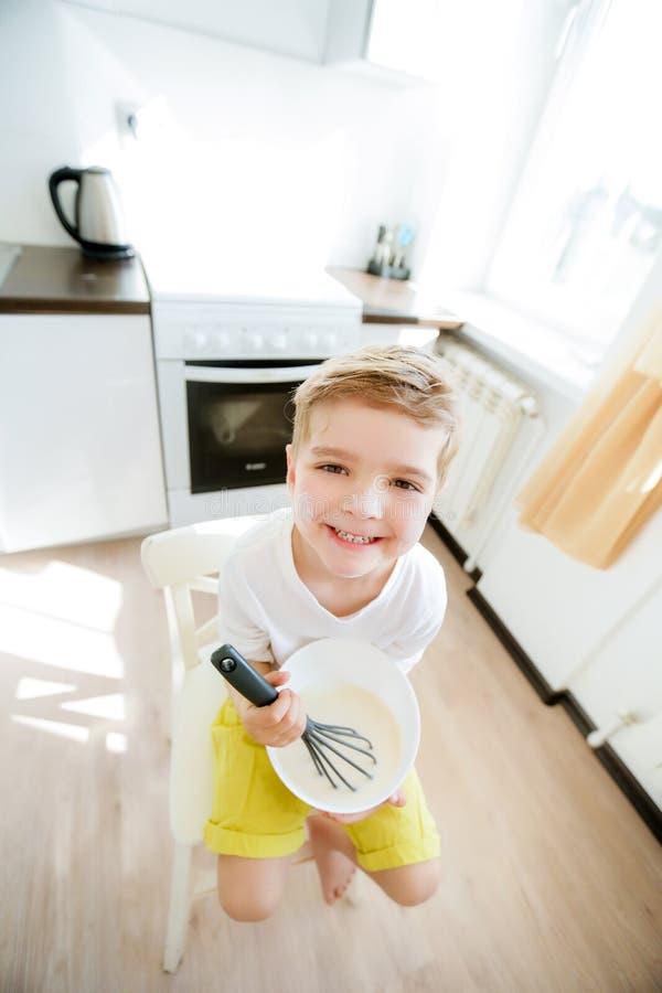 Сладкий ребенок дошкольного возраста, помогая его маме в кухне, делая блинчики в утре, счастливое детство стоковая фотография rf