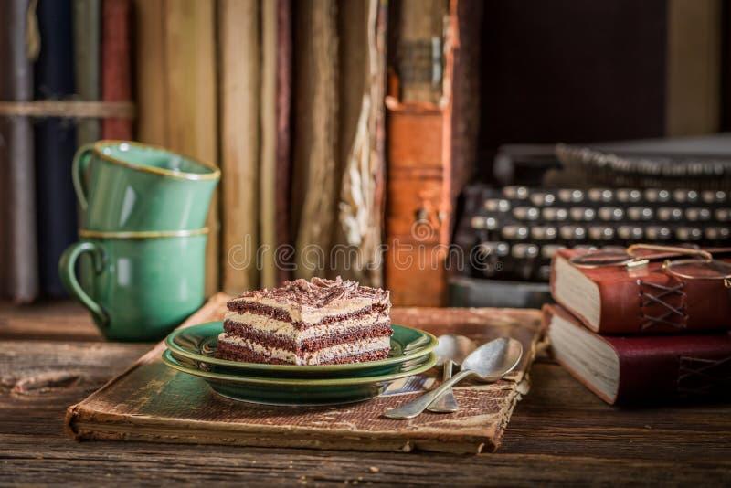 Сладкий шоколадный торт с кофе, книгами и машинкой стоковая фотография