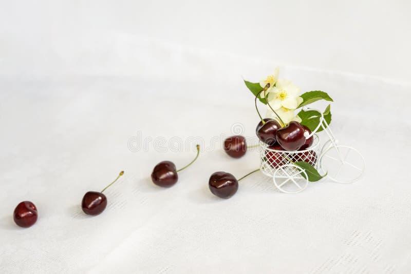 Сладостная зрелая расслоина вишни из миниатюрной игрушки, крупного плана вагонетки на светлой предпосылке, цветках, листьях, взгл стоковое изображение