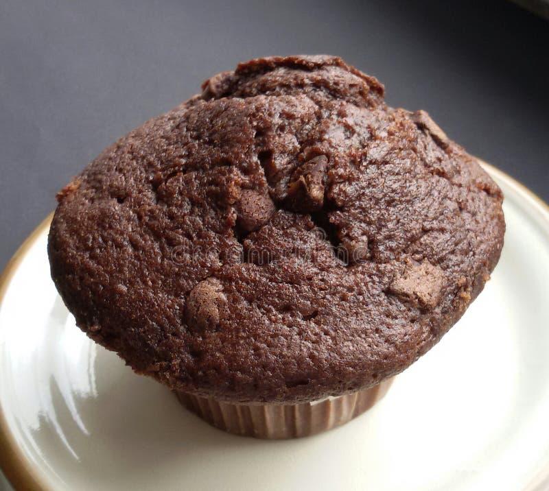 Сладостная и вкусная булочка шоколада на плите над черной таблицей стоковая фотография
