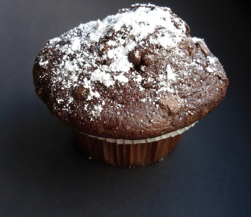 Сладостная и вкусная булочка шоколада с напудренным сахаром на черной таблице стоковые фото