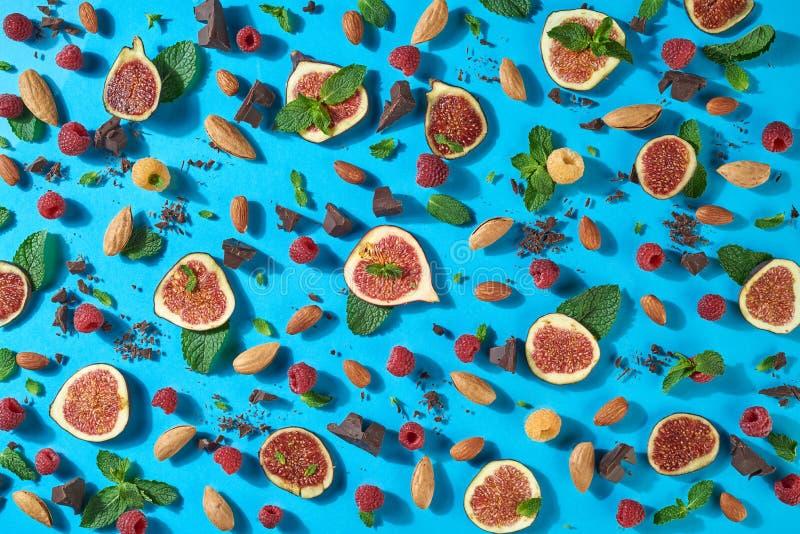 Сладостная картина десерта от смокв ripr, гаек, шоколада, свежей поленики, лист значенный на голубой предпосылке Плоское положени стоковое фото rf