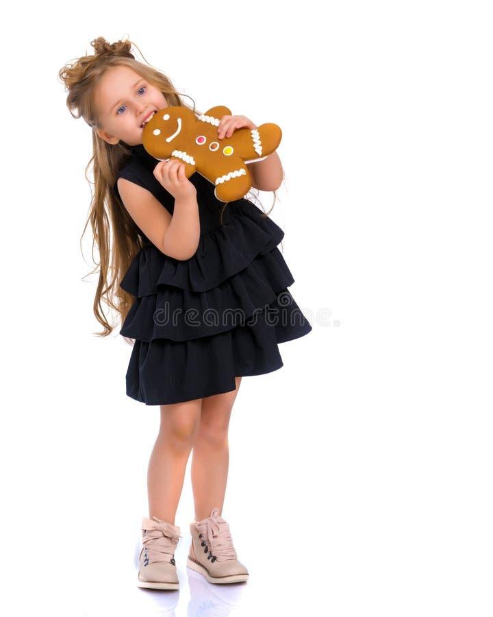 Сладостная маленькая девочка ест пряник стоковое изображение