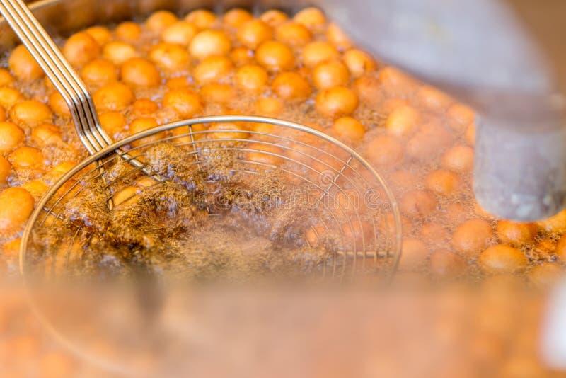 Сладостные глубоко зажаренные золотые донуты donuts в горячем кипя масле Tak стоковая фотография rf