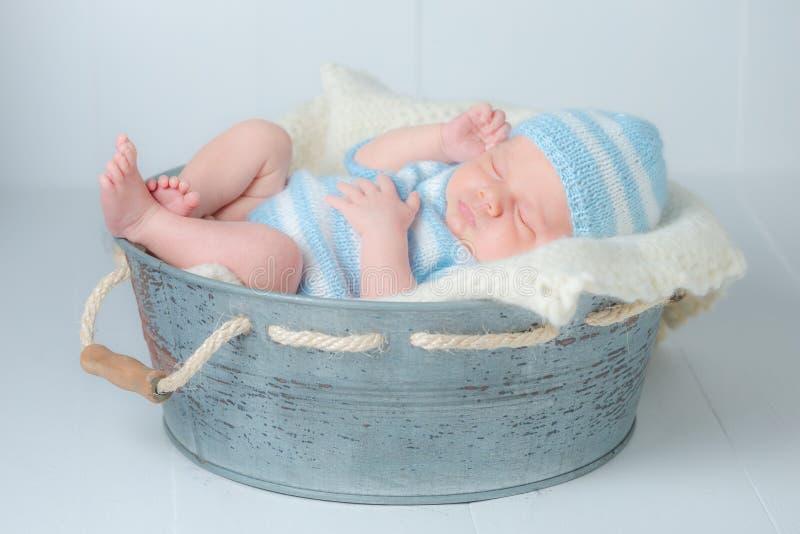 Сладостный newborn младенец спать в меньшей ванне стоковое изображение