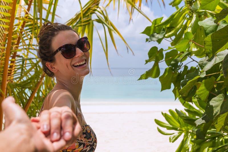 Следовать мной концепция молодой женщины идя к пляжу в тропическом назначении Смеяться к камере стоковое фото rf