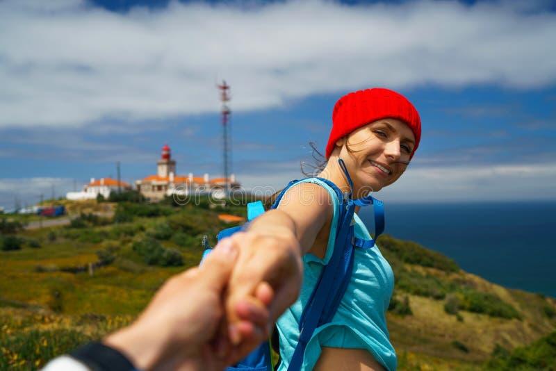 Следовать мной - счастливая молодая женщина в красной шляпе и с рюкзаком b стоковое фото rf