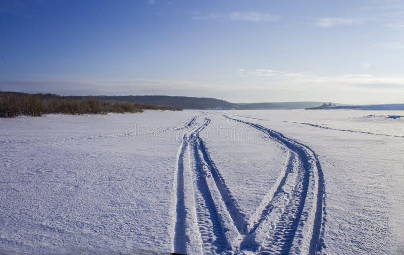 Следы на льде реки от снегохода стоковые фото
