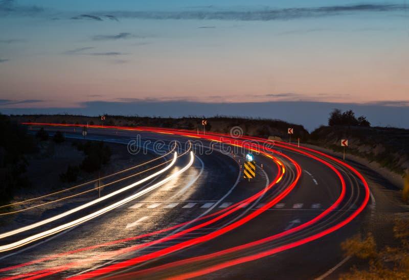Следы света на кривой шоссе стоковая фотография rf