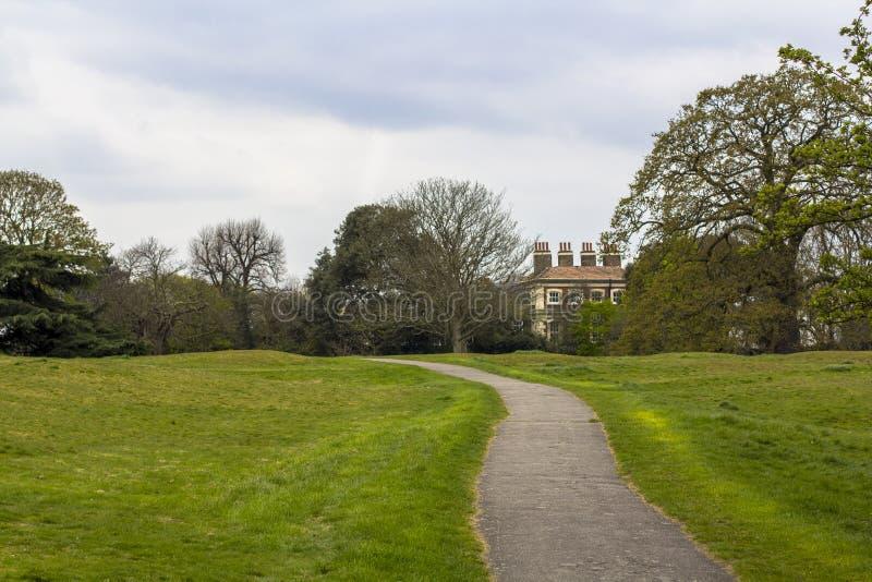 След в парке Гринвич, путь среди зеленых лугов и деревья Имущество в глубинах парка стоковые изображения