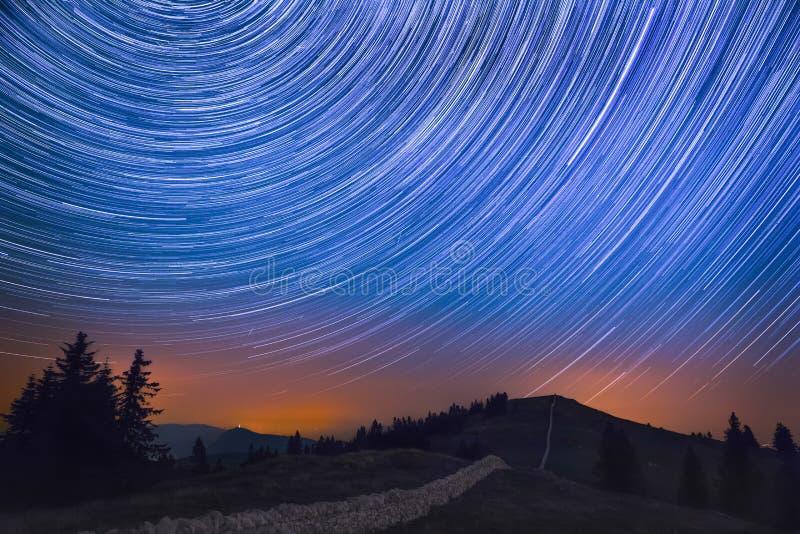 След звезды над горой и изрезанным ландшафтом с крестом метеоров стоковая фотография rf