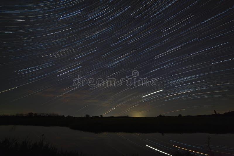 След звезд в ночном небе с облаками отраженными в реке Движение в космосе сфотографированном на долгой выдержке стоковое изображение