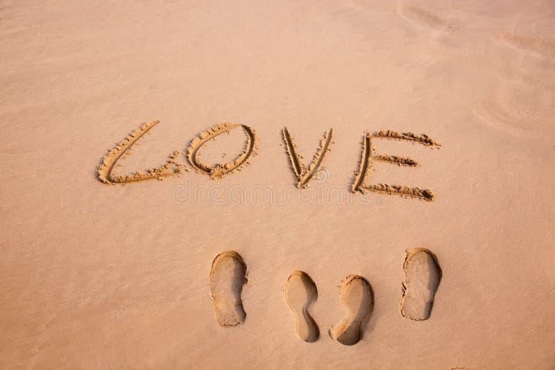 След ноги и влюбленность написанные в песке на пляже стоковая фотография