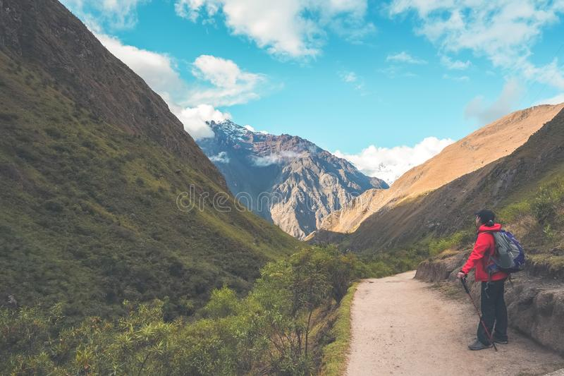 След Inca, Перу: 11-ое августа 2018: Женский hiker принимает остатки и смотрит красивый вид за ей Она на пути стоковые фото