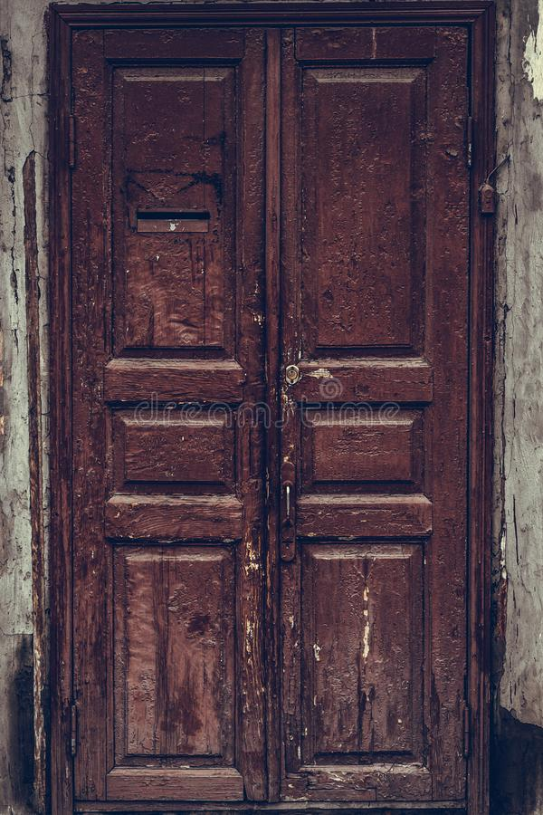 Слезать коричневую деревянную дверь Разрушанная деревянная дверь grunge с треснутой maroon краской Изношенное темное - красная дв стоковое изображение