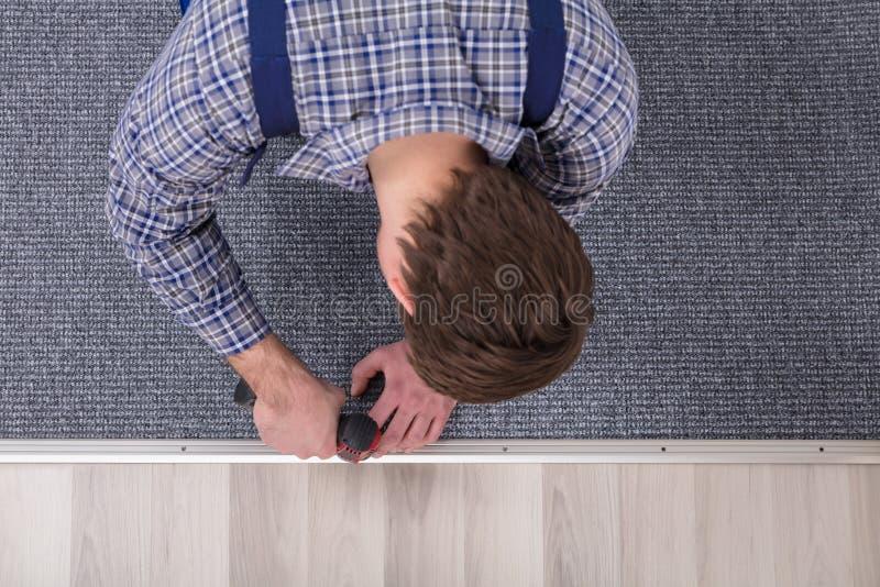 Слесарь-монтажник ковра устанавливая ковер с беспроволочной отверткой стоковое изображение
