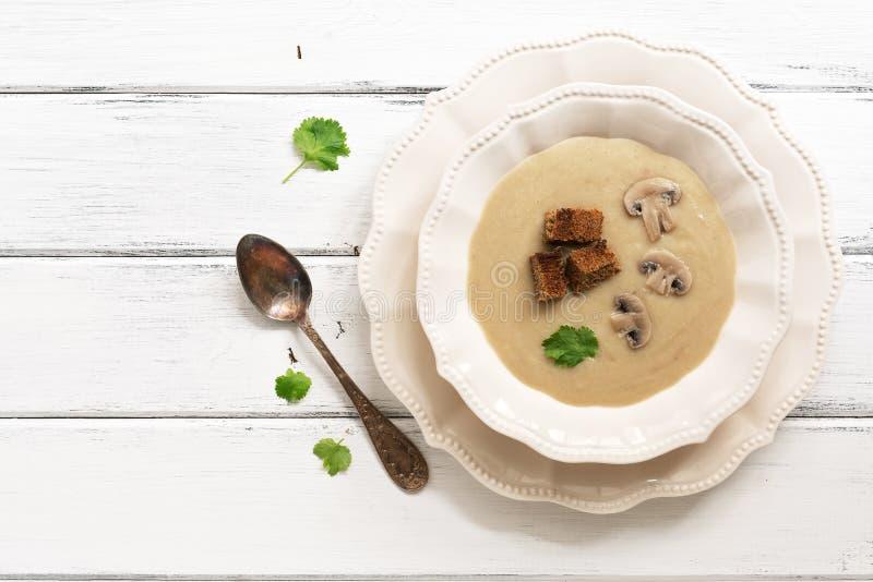 Сливк супа гриба, который служат в белой плите на белой деревянной деревенской таблице Зима грея горячий суп Взгляд сверху, плоск стоковое изображение