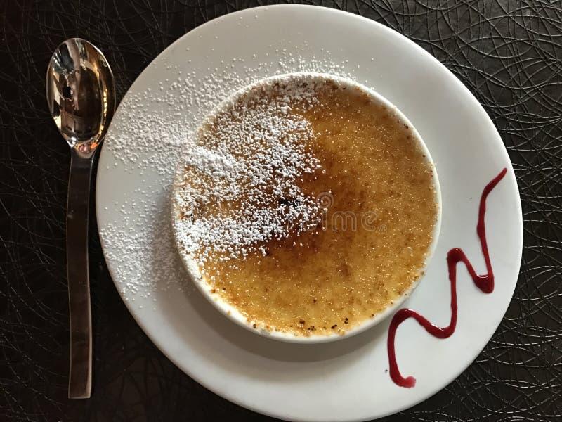 Сливк-brulee в белой чашке с ложкой стоковые фото