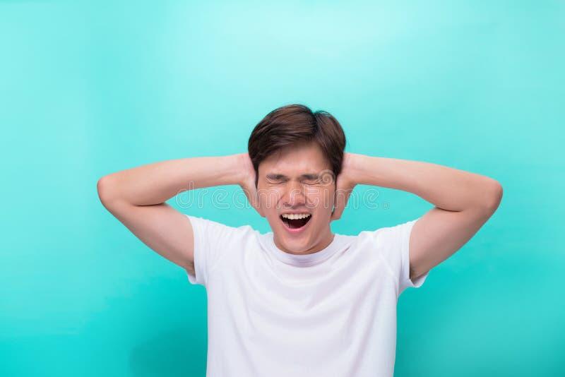 Слишком громко Разочарованный молодой человек покрывая уши с руками и смотря камеру пока стоящ серая предпосылка стоковые изображения rf