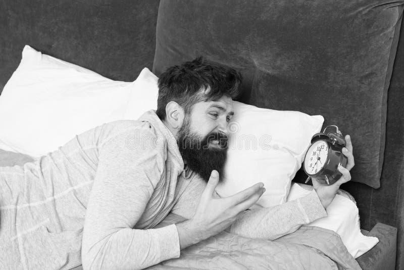 Слишком раньше бородатый будильник ненависти человека пока лежащ в кровати дома человек с будильником бодрствование утра вверх Со стоковые изображения