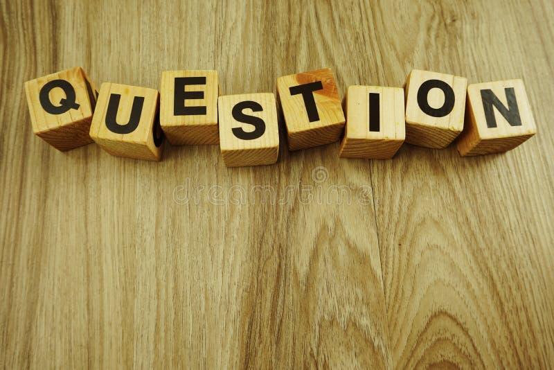 Слово вопросов в деревянных письмах алфавита куба на деревянной предпосылке стоковые фотографии rf