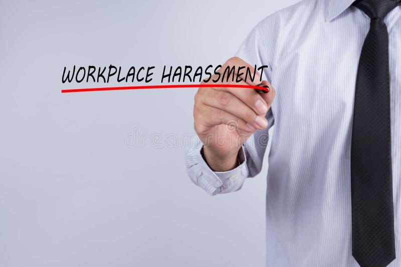 Слово домогательства рабочего места сочинительства руки бизнесмена с красной отметкой на прозрачном обтирает доску, концепцию дел стоковая фотография