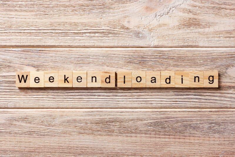 Слово загрузки выходных написанное на деревянном блоке Текст на таблице, концепция загрузки выходных стоковые фото
