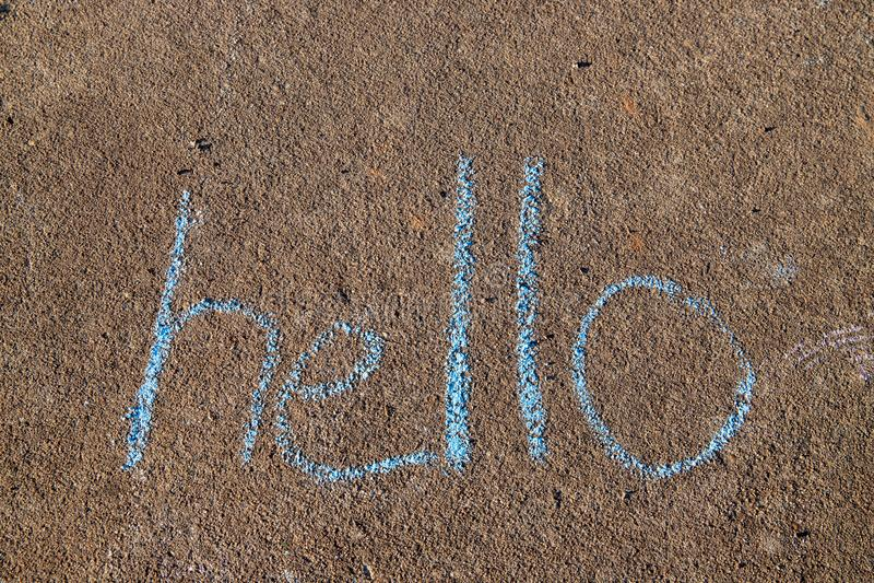 Слово здравствуйте написанное с мелом тротуара на серой предпосылке конкретной мостовой стоковые фотографии rf