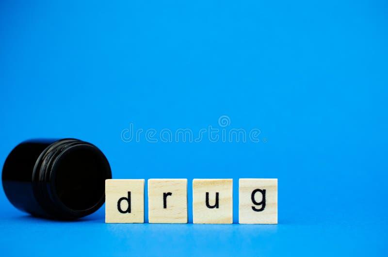 Слово ЛЕКАРСТВО на деревянных кубах и медицинской темной склянке на голубой предпосылке r стоковая фотография rf