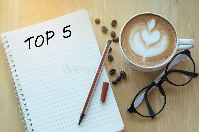 Слово 5 лучших на тетради с стеклами, карандашем и кофейной чашкой на wo стоковое изображение