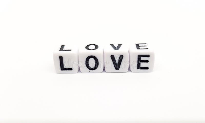 слово любов построенное с белыми кубами и черными буквами на белой предпосылке стоковая фотография