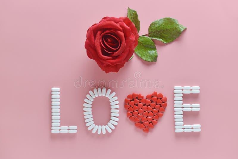 Слово ЛЮБОВ сделанное из таблеток и красной розы медицины на розовой предпосылке Концепция дня ` s валентинки стоковые фото