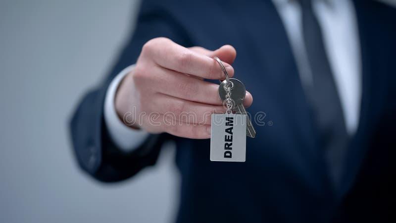 Слово мечты на keychain в руке бизнесмена, складе ума к достижению цели, крупном плане стоковые фотографии rf