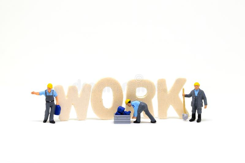 Слово работы от деревянных писем и миниатюрного работника на белой предпосылке Сцена концепции работы синего воротничка стоковое изображение
