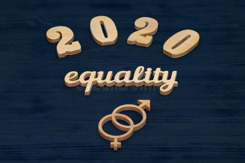 Слово РАВНОСТИ высекаенное из переклейки Символ равенства полов Черная деревянная предпосылка 2020 стоковые изображения