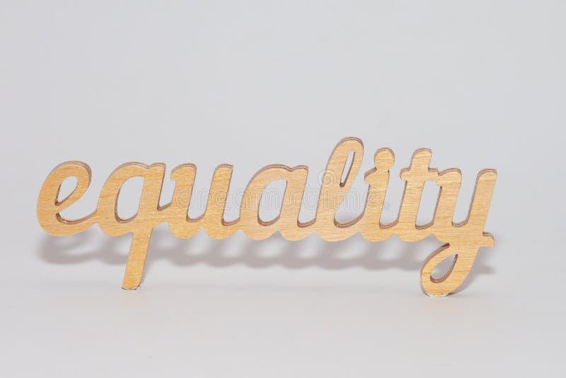 Слово РАВНОСТИ высекаенное из переклейки Символ равенства полов o стоковое фото