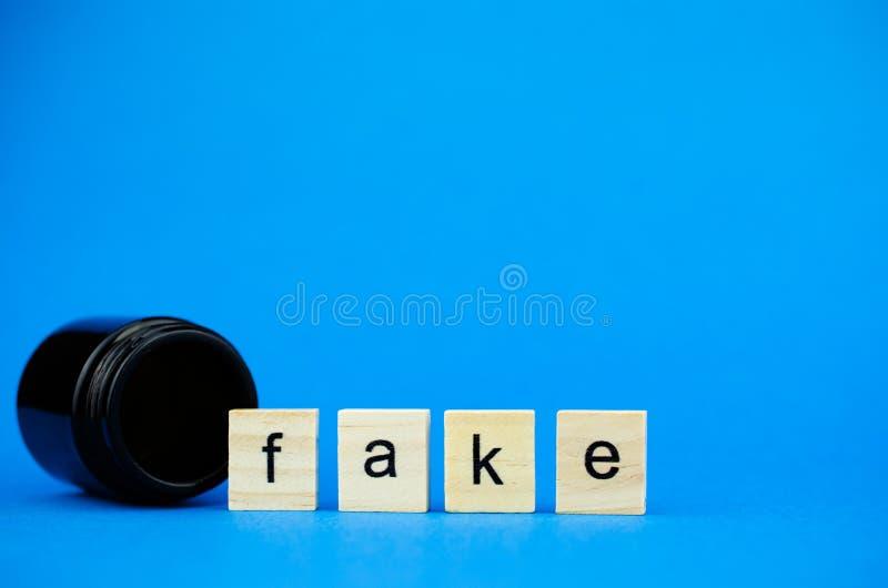 Слово ФАЛЬШИВКА на деревянных кубах и медицинской темной склянке на голубой предпосылке Медицинская концепция поддельных лекарств стоковая фотография rf
