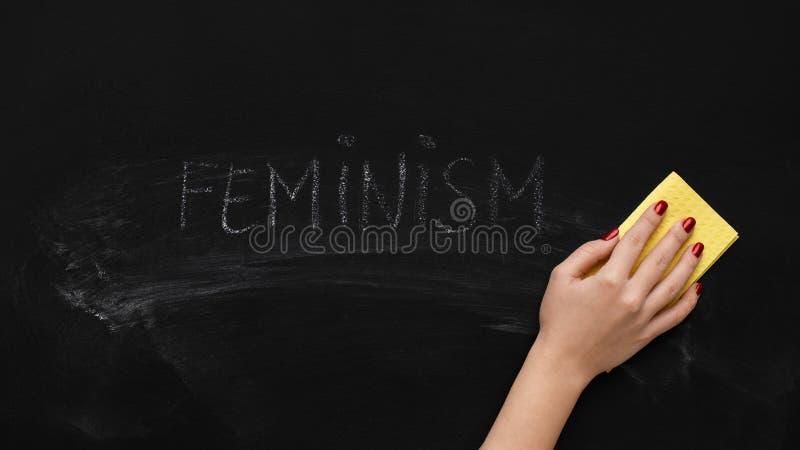 Слово ФЕМИНИЗМ на доске, панорама женщины очищая стоковые фотографии rf