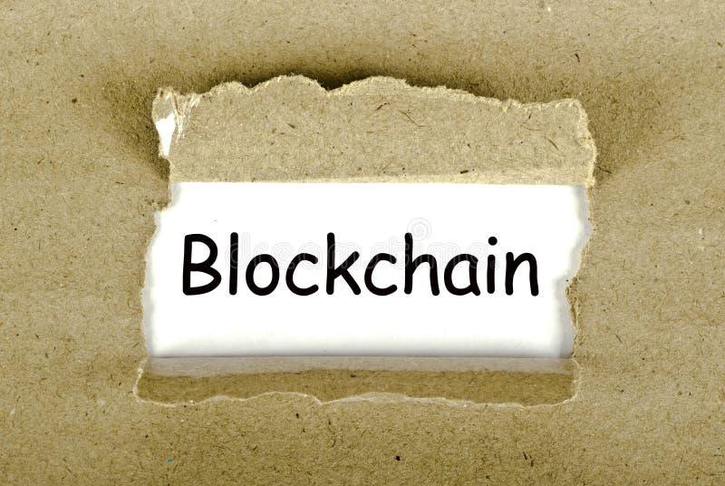Слово Blockchain написанное в бумажном отверстии бесплатная иллюстрация