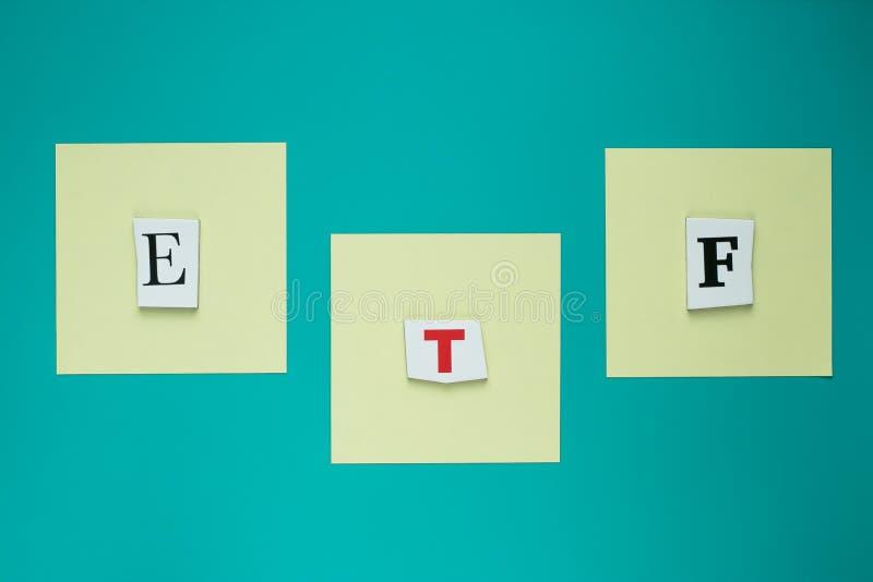 Слово ETF от отрезанных писем на голубой предпосылке Текст сочинительства слова - ETF Знамя с надписью - ETF Начало распределения стоковое фото rf