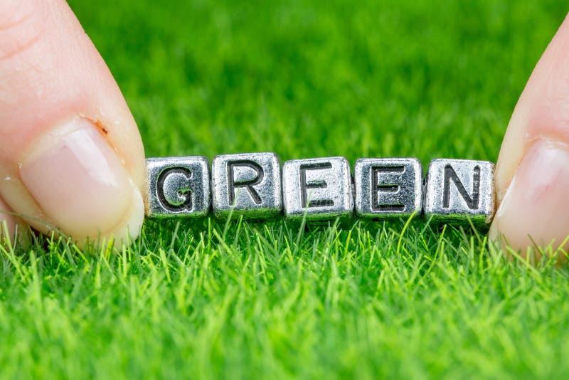 Слово GREEN написано металлическими буквами, которые лежали на траве и удерживались между пальцами женщины Концепция экологическо стоковые изображения
