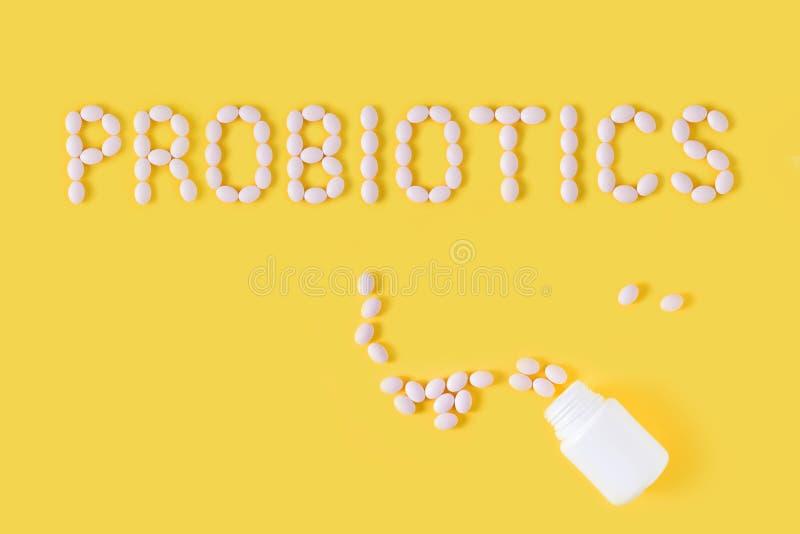 Слово Probiotics сделанное пилюлек на желтой предпосылке Плоское положение, взгляд сверху, космос бесплатной копии стоковое изображение