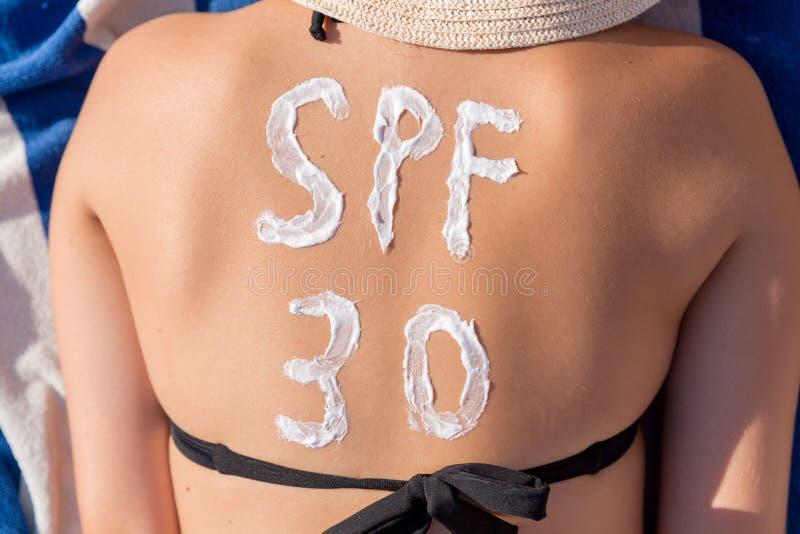 Слово Spf 30 нарисовано с sunblock на задней части женщины лежа на sunbed на пляже Концепция фактора предохранения от Солнца стоковые изображения rf