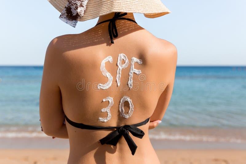 Слово Spf 30 нарисовано с sunblock на задней части женщины ослабляя на пляже стоковые изображения