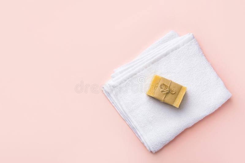 Сложенное мыло марселя чистого белого пушистого ремесленника полотенца Terry handmade на пастельной розовой предпосылке стоковая фотография