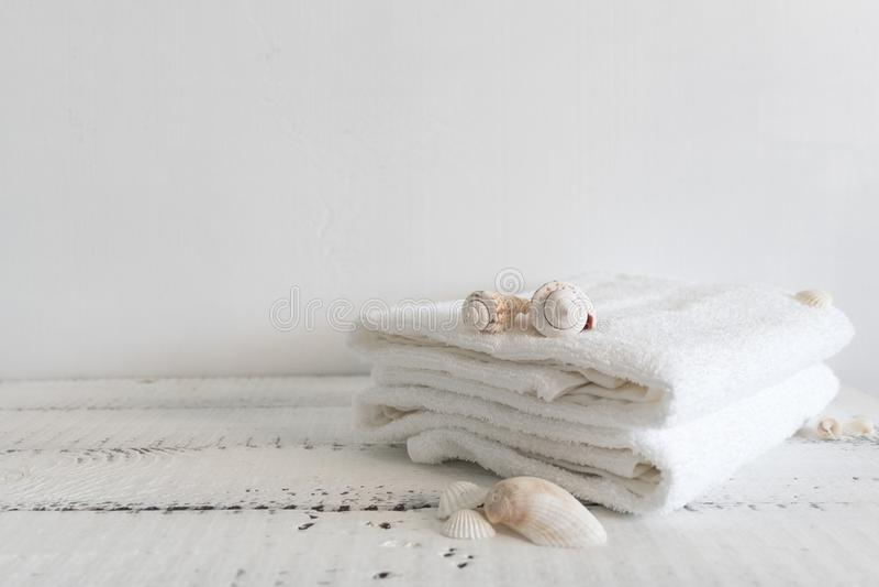 Сложенные белые полотенца и различные seashells на белом деревянном столе Курорт и здоровье, ткань Terry хлопка экологическо стоковая фотография rf