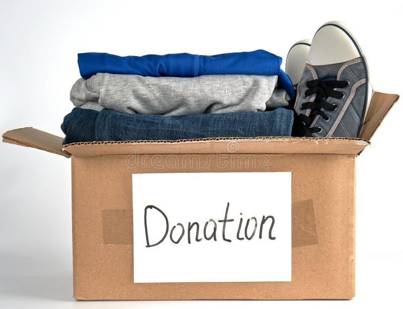сложенные одежды в коричневой бумажной коробке с пожертвованием надписи стоковое фото rf
