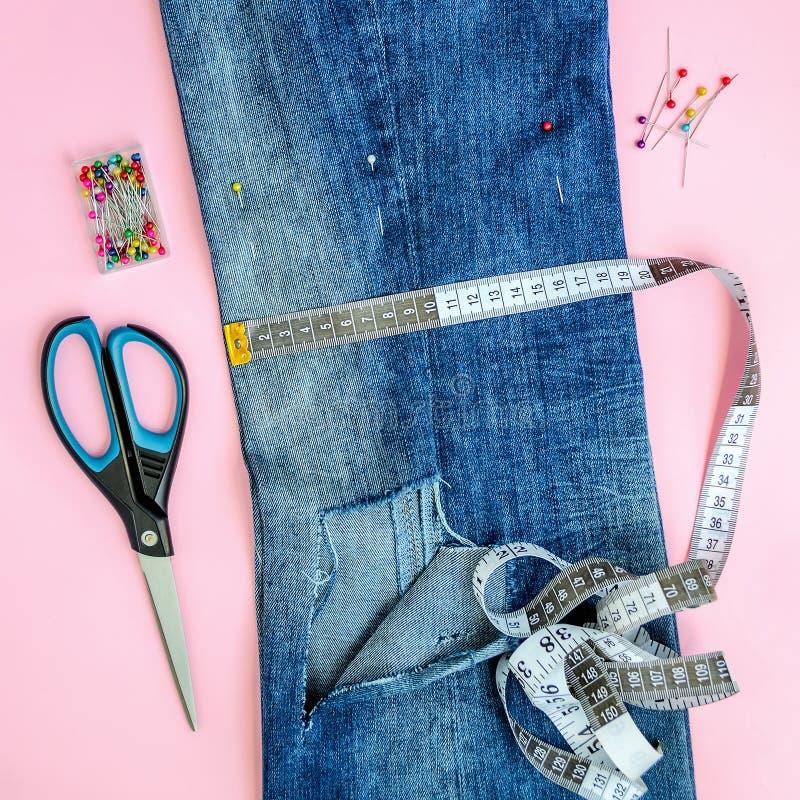 Сложенный в половинных голубых джинсах с большим отверстием на ноге тяжелого дыхания, шить штырях, ленте портноя и ножницах стоковое фото