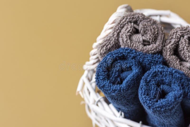 Сложенный свернул чистые полотенца washcloth Terry хлопка в плетеной корзине на прованской зеленой предпосылке стены bathroom Нул стоковые фотографии rf